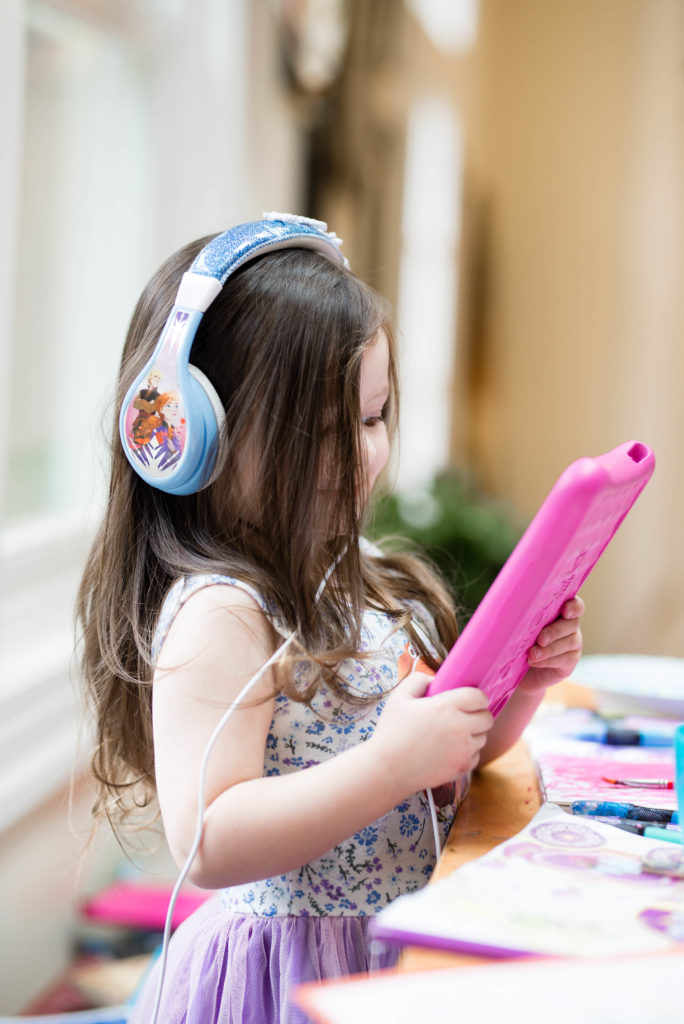 young girl listening to an audiobook with fire amazon tablet - best audiobooks for kids and tips for how to get started