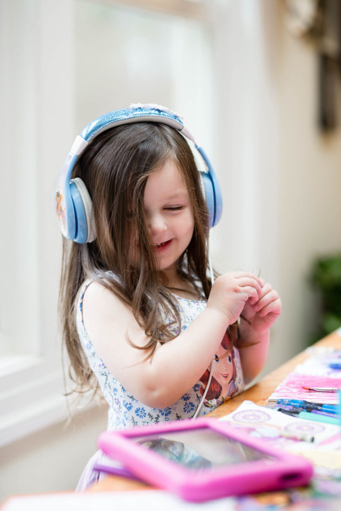 young girl listening to audiobook on fire tablet with headphones and smiling - best audiobooks for kids and tips for how to get started
